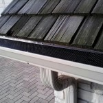 Seamless gutter with leaf protection. Also elbow and downspout coming from the middle